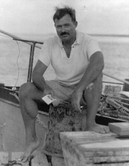 Ernest Hemingway sitting on a dock next to his boat, Pilar, in the 1930s